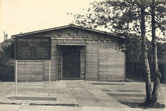 Townley Rd Baptist Chapel before exterior brick surface added on. Note how some of the grave stones from the previous site have been inlaid at the large frontage